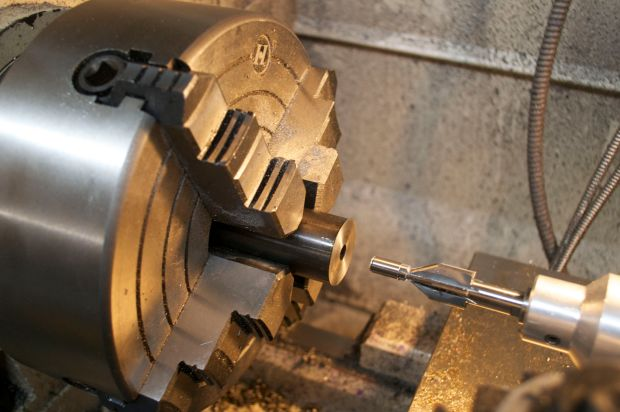 A 60-degree piloted center drill is used to cut a chamfer that will mate to the centers used on the lathe.  It is secured in a Manson floating reamer holder.
