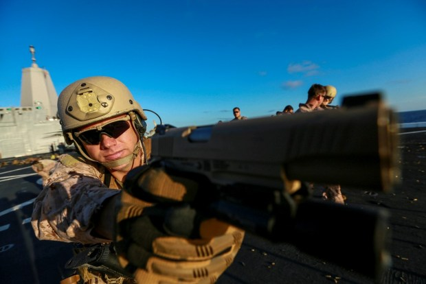 U.S. Marine Gunnery Sgt. Mickey Eaton sights in with his M1911 .45 caliber pistol at a target during Composite Training Unit Exercise (COMPTUEX) aboard the USS Anchorage (LPD 23) off the coast of San Diego March 23, 2015. Eaton is the assistant operations chief of the 15th Marine Expeditionary Unit's Maritime Raid Force. The 15th MEU's MRF Marines constantly sharpen their skills with different weapon systems to maintain a high level of readiness. (U.S. Marine Corps photo by Sgt. Jamean Berry/Released)