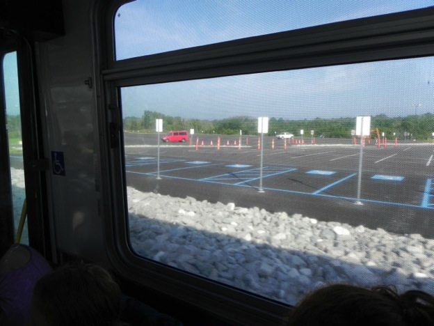 This image shows a shot taken from inside a vehicle out onto the parking lot of the Ark Encounter exhibit. There is one SUV vehicle parked in the distance in the entire parking lot. The lot is partitioned by various traffic cones scattered throughout the lot. In front of the vehicle from which the photo was taken are a layer of large pieces of gravel followed by handicap parking spaces with accompanying signs indicating handicap parking. There is a horizon of trees in the background of the photo along with a partly cloudy sky.