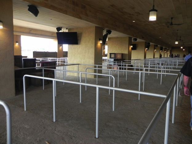 This image shows an angled shot of a mostly empty metal line queue at the entrance to the Ark Encounter exhibit. There are two men that are partially visible to the right of the line queue, as well as a small group of five or six people on the far end of the line queue. There are rectangular columns in series in the middle of the line queue, each with televisions that are off as well as speakers attached to them. There is a rectangular window in the background on the left of the picture with columns in series displaying hanging lights in front of it. There are a group of dark wooden boxes on the left of the picture closer to the camera beside the line queue.