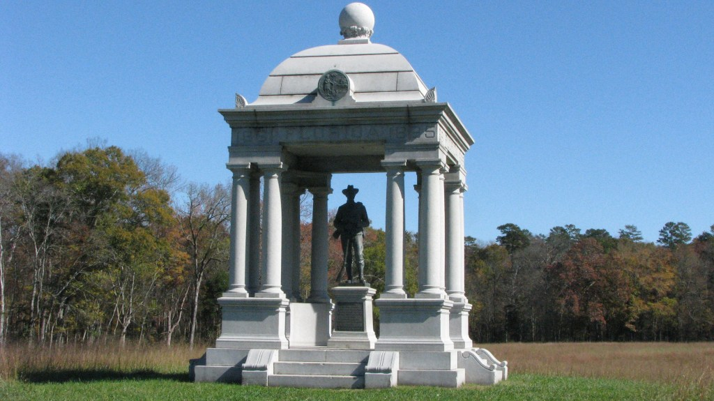 This image shows a confederate monument with 12 columns - three in each of the four corners - and a dome top. Inside the dome is a bronze statue of a confederate soldier.