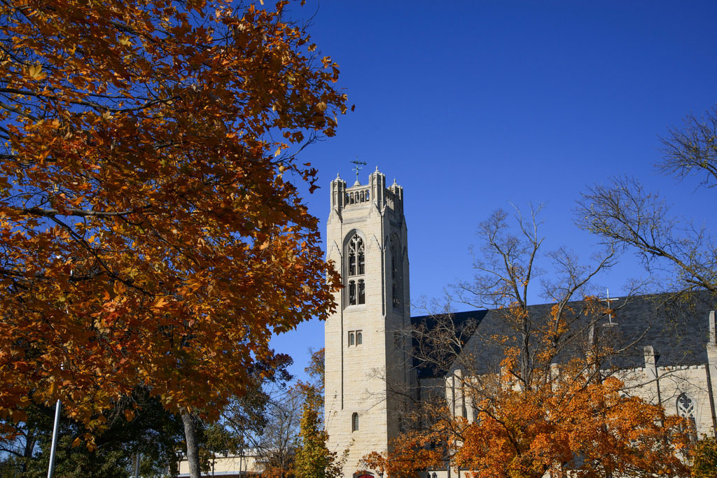 This image features a bell tower of a chapel on the campus of College of the Ozarks. It was taken during autumn, as there are brownish-orange leaves on the nearby trees.