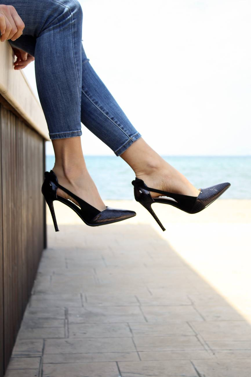 woman in blue denim skinny jeans and black stiletto shoes