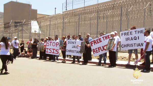 Members of California's Iraqi Christian community and their supporters protest the months-long detention of Iraqi Christian asylum-seekers at the Otay Mesa detention center. (Image source Al Jazeera video screenshot)