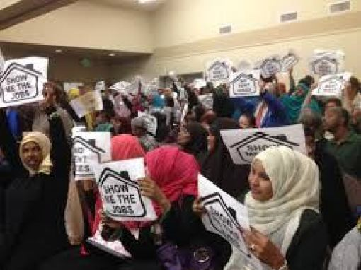 "Coming to Montana once the IRC has a foothold! This is the IRC's handiwork in Seattle! Somali refugees have gobbled up much of the public housing and are protesting a plan that would require them to pay a little more for that housing when they find a job. Signs in the back say ""No Rent Hike."""