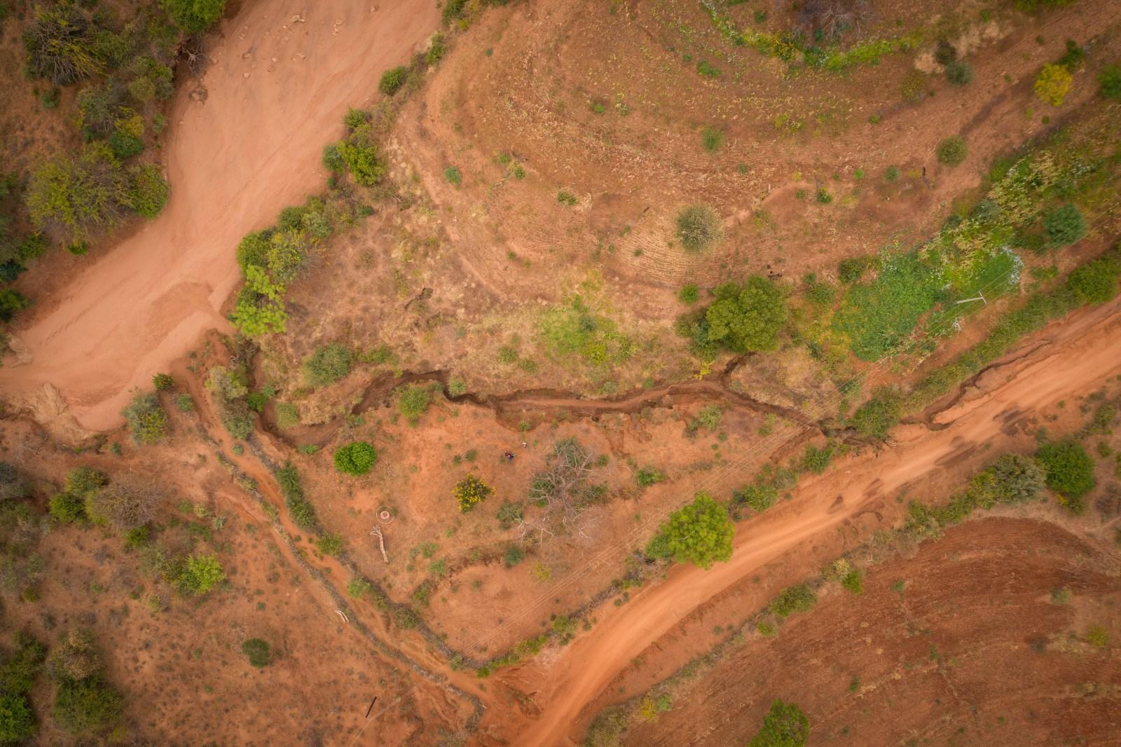På den här drönarbilden syns det tydligt hur gården har blivit uppdelad i två delar. Den nedersta delen kan han inte längre använda på grund av uppdelningen som vattnet har gjort. Han har lönlöst försökt leda om och stoppa vattnet. Tyvärr var det här ett ganska vanligt problem i det här området.