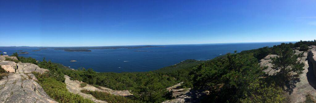 A panoramic view of the mountains, trees, and ocean from the top of the Precipice Trail