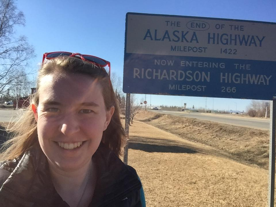 Riley poses with a sign marking the end of the road, 1,422 miles later