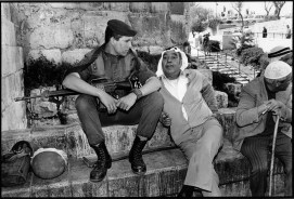 At an entrance to the old city of Jerusalem, a Palestinian and an Israeli sit together and talk.