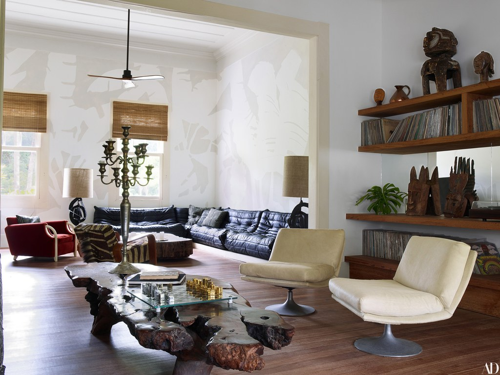 In the living room, an antique pewter candelabra sits atop a reclaimed redwood table from Todd Merrill Studio. Murals by artist Chris Wyrick