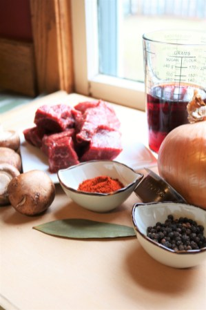 A braise ingredient combination: beef chuck, mushroom, onion, port, beef stock concentrate, a bay leaf, paprika, and black pepper.