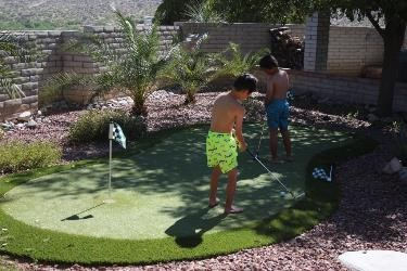 How to plan your family vacation on a budget|Two boys in bathing suits on a putting green