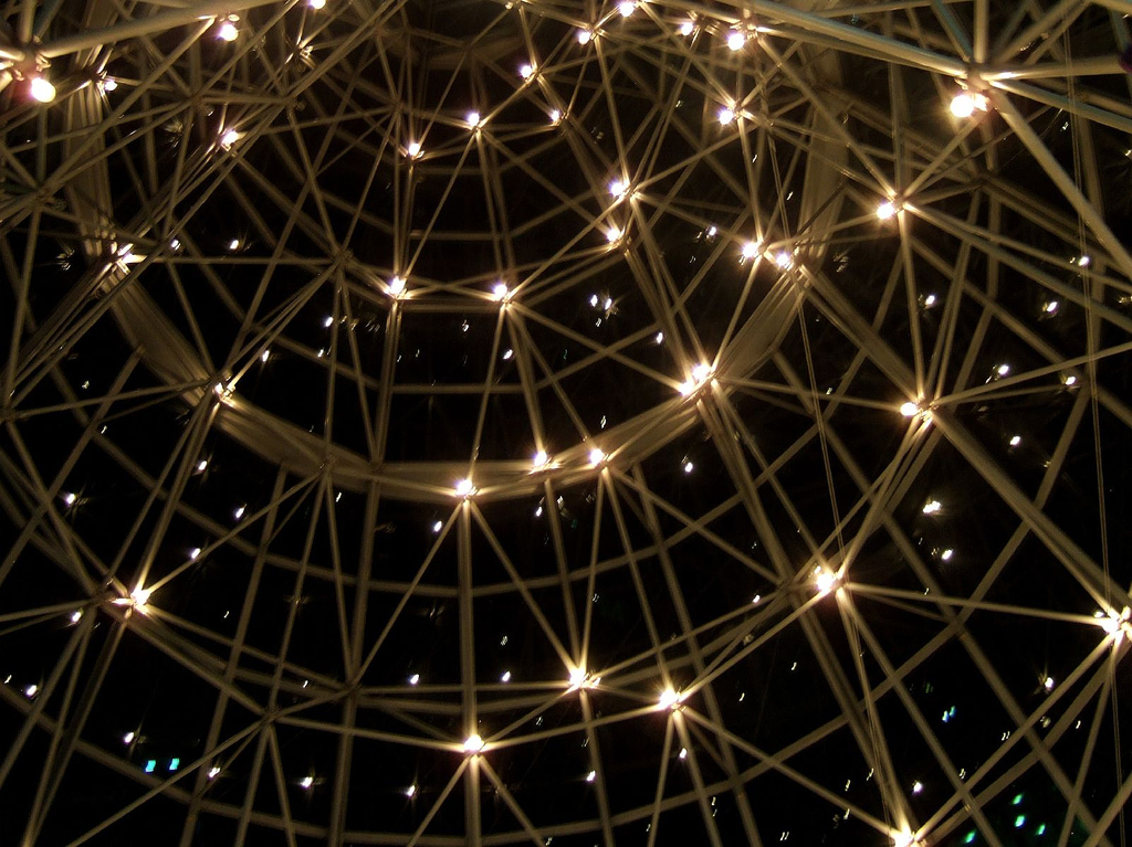 Looking up at a glass roof with lights and out to the night sky with many stars