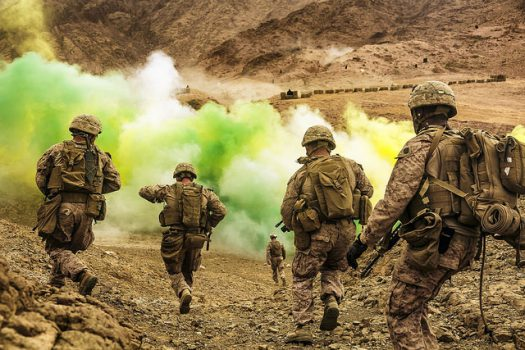 Five soldiers in camouflage with backpacks and helmets walking towards a large cloud of green yellow and white dust gas.