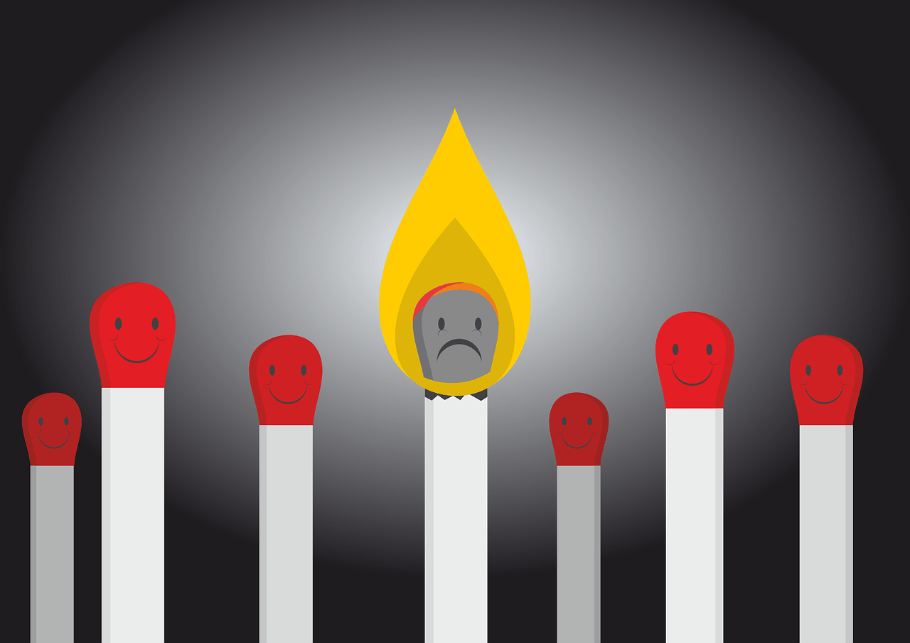 cartoon of unlit, smiling matches with one match in the centre on fire with a sad face