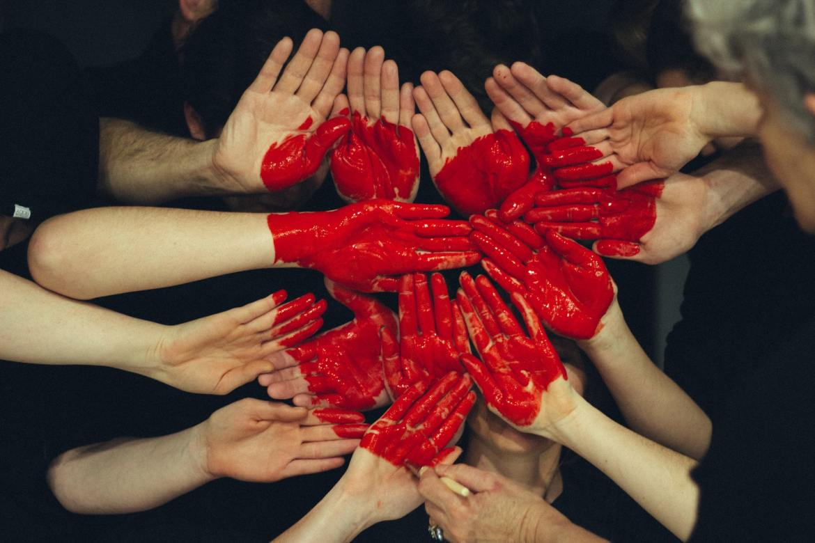 many hands grouped together with a red heart painted across them