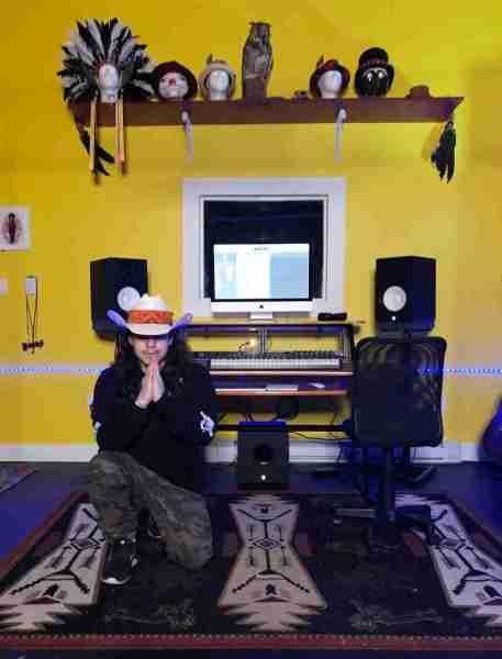 Joseph Laplante kneeling in his Ble$$ed Street Studios