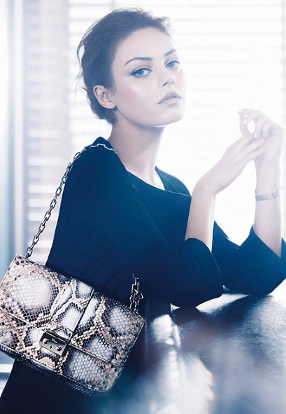 Actress Mila Kunis models a Miss Dior snakeskin handbag.