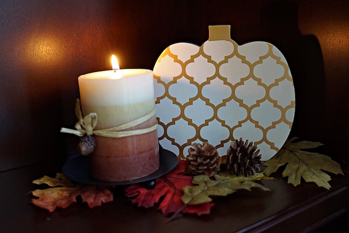 fall decor scene with pumpkin and candle