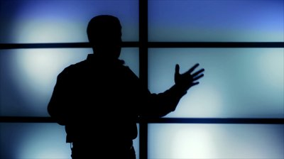stock-footage-silhouetted-against-tinted-dark-blue-panels-a-man-paces-about-gesturing-as-if-delivering-a-speech
