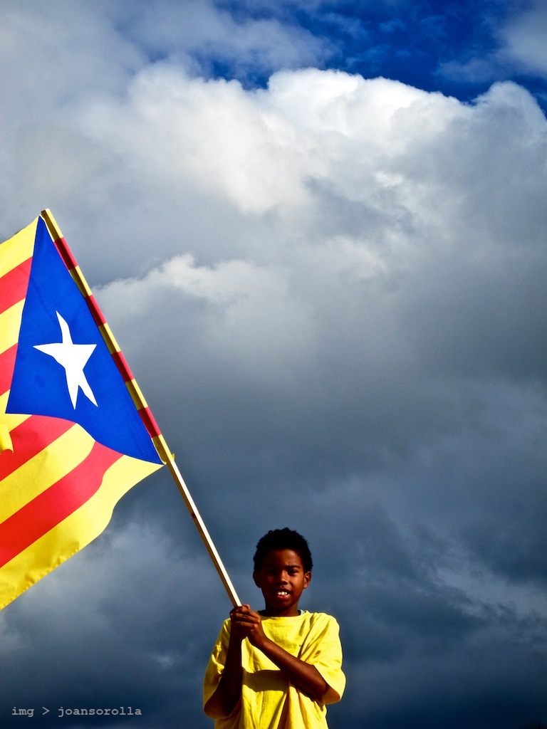 A young boy holds the flag associated with Catalonian Independence. Photo Credit: Joan Sorolla/ Flickr (CC By 2.0)