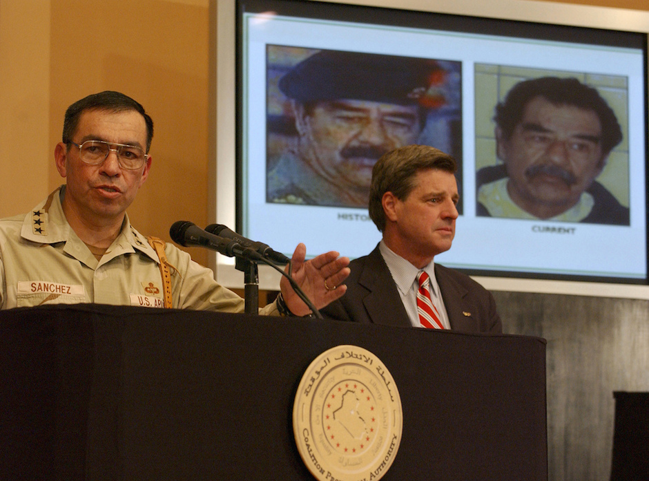 Lt. Gen. Ricardo Sanchez and Ambassador L. Paul Bremer (R), talk to reporters at the Baghdad Forum, Dec. 14, 2003, about the capture of Saddam Hussein. Photo Credit: U.S. Army Europe Images/ Flickr (CC BY 2.0)