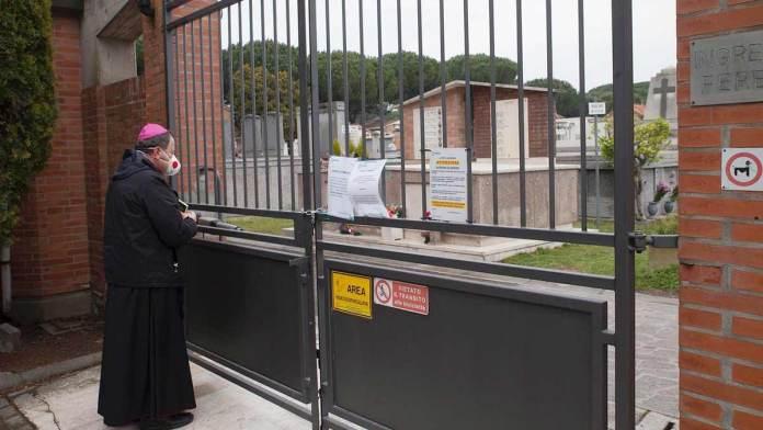 Monsignor Ghizzoni davanti ai cancelli del cimitero monumentale