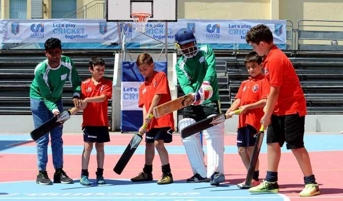 Istruttori e ragazzi durante il cricket