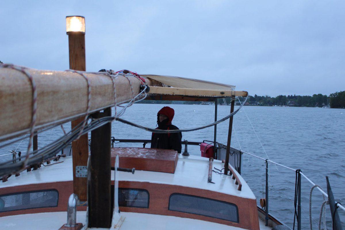 Rith mit gelegtem Mast um Regen auf dem langen See