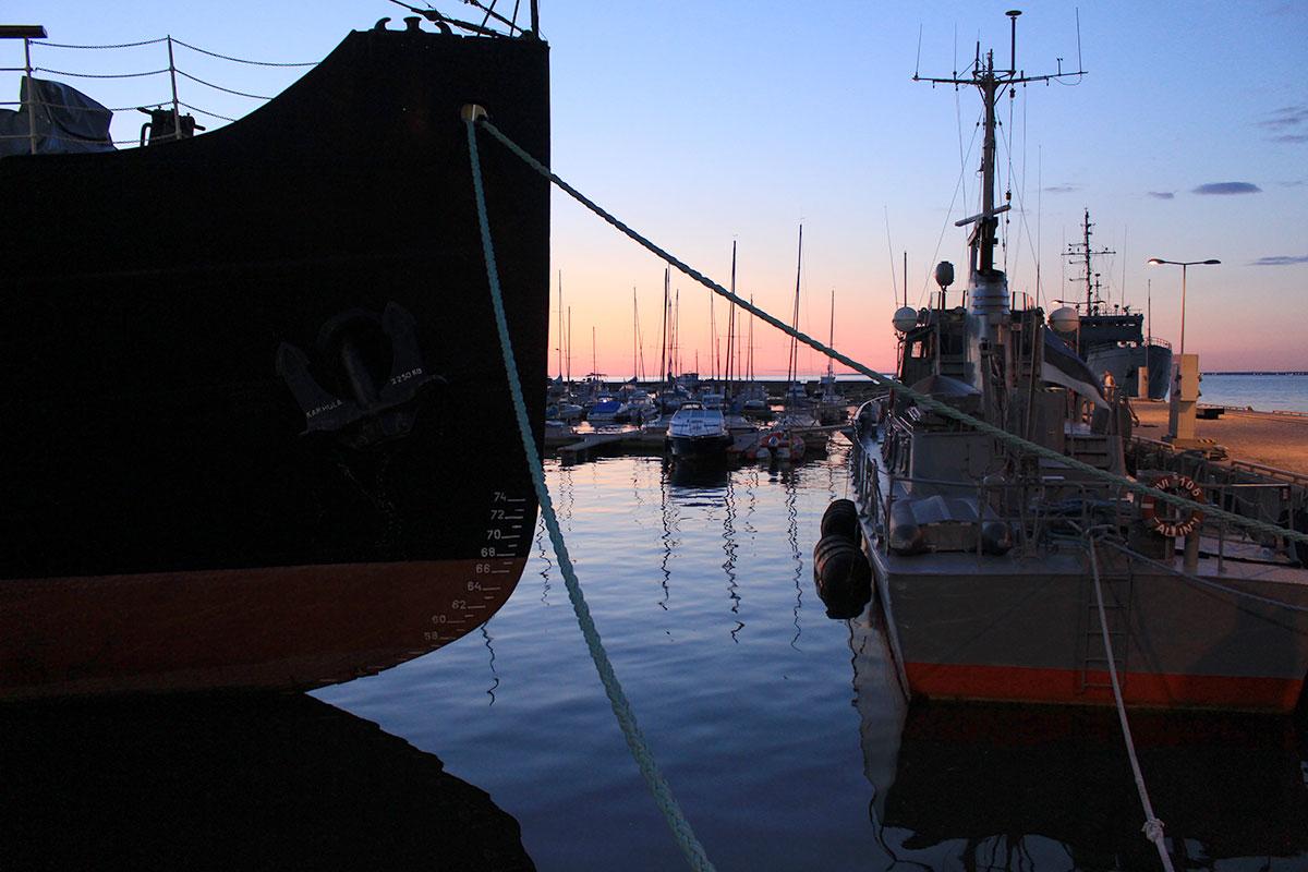 Blick ins Abendrot im Hafen von Tallinn mit großen und kleineren Schiffen im Gegenlicht