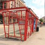 Ein Buswartehäuschen aus roten Metallstreben und Glas