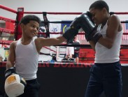 Giovanni playfully punches Cory in between practice sets on the punching bag.