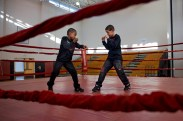 """(Boxing Brothers - 1 - Boxing gave Jay'von and Fynest Cummings energy and vitality, despite the obvious harm it caused to others and themselves. Jay'Von Cummings, 10, and Fynest Cummings, 8, are brothers who have attended classes at Future Boxing Club in Rochester, N.Y. since Feb. of 2014. Their father, Larry Cummings, 32, coaches his son's in their makeshift gym in their basement and cuts their hair before their big matches. Jay'Von and Fynest both look up to each other for help in both school, growing up and boxing. Jay'Von placed second in 2015 at the Silver Gloves and hopes to place first this Saturday and Sunday, Dec. 3 & 4. This year will be Fynest's first time entering the Silver Gloves.) Fynest Cummings, 8, (left) and Jay'Von Cummings, 10, (right) practice in the ring before the N.Y. State Silver Gloves Boxing Tournament at Wilson Foundation High School begins in Rochester, N.Y., on Dec. 4, 2016. """"His strengths are my weaknesses, we are always learning from one another,"""" says Jay'Von."""
