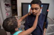 """Nunu brushes his brother Joma's face with blush at their home in Batavia, N.Y., on Dec. 11, 2016. Nunu's siblings, two older brother and a younger sister, all accept him for who he is. His brothers often need to defend him during times of bullying. """"They don't judge me about it,"""" said Nunu, """"And I can aways get help about people teasing me."""""""