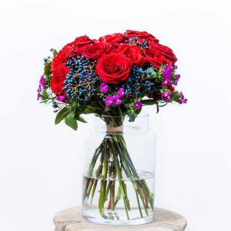 Raudonų rožių puokštė stiklinėje vazoje