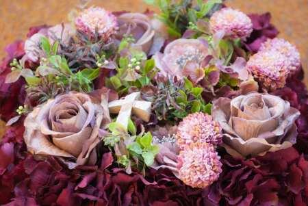 Rusvos spalvos dirbtinių gėlių pagalvėlė (iš arti)