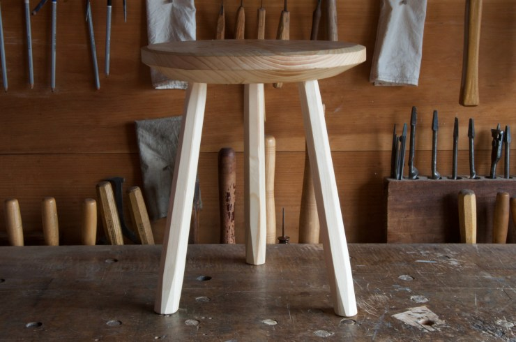 A three-legged staked stool is displayed on the workbench at RivenJoiner.com.