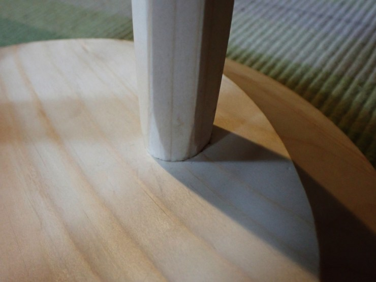 A closeup of the leg joint of a three-legged staked stool at RivenJoiner.com.