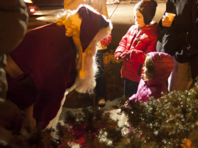 "TURNERS FALLS (December 12, 2014) — Santa leans to talk to a little girl on Avenue A in Turners Falls during Friday night's ""It's a Wonderful Night"" celebrations. Santa arrived in a fire truck and handed out candy canes to children. Recorder/Trish Crapo"