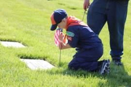 Kaden Linnen, 7, places a flag