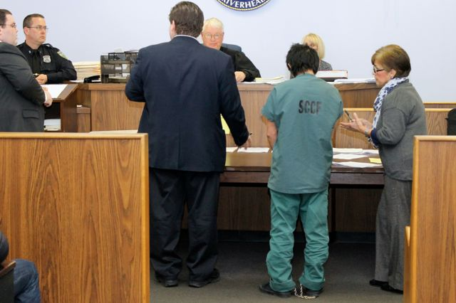 A prisoner is brought before Riverhead Town Justice Allen Smith Monday. With him is the court's Spanish interpreter Zyta Piegari. (RiverheadLOCAL photo by Denise Civiletti)