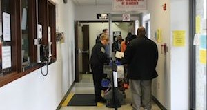 People wait in line to be scanned in the hallway outside the entrance to Riverhead Justice Court Monday. (RiverheadLOCAL photo by Denise Civiletti)