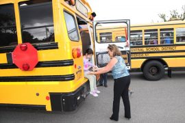 Colette Furcht, Transportation Co-Director helps a student during Phillips Avenue School's bus drill