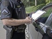 A police officer gives a speeding ticket to a driver.