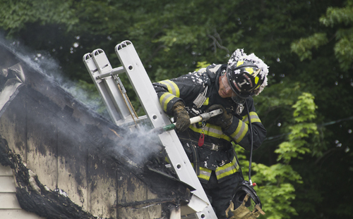 A Jamesport firefighter knocks away part of the charred roof at a fire on Herricks Lane Wednesday afternoon. (Credit: Paul Squire)