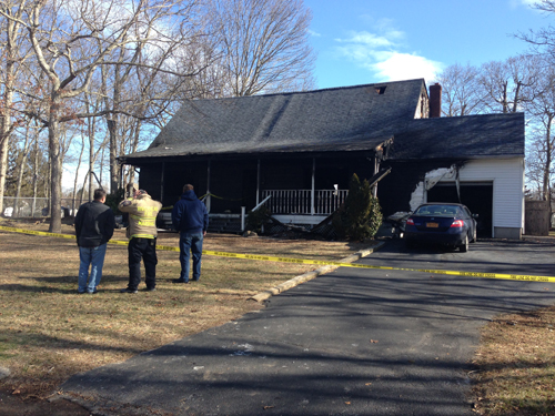 PAUL SQUIRE PHOTO | Riverhead Fire Marshals investigate the scene of Monday morning's house fire.
