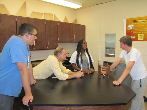 Andrew Hubner of Shoreham-Wading River High School, physics teacher Andrew Kolchin, Asia McElroy from Riverhead High School and former Riverhead High School student Phil Becker of Bay Shore do some experiments with Newtown's Cradle Friday at BOCES' new Regional STEM high school in Bellport. (Credit: Tim Gannon)
