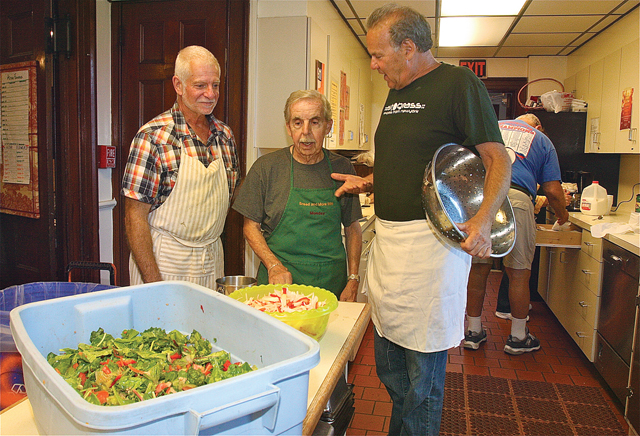 Bread and More co-president Bennett Brokaw talks to volunteers John DeFrancis (left) and Joe Desio before dinner service Monday afternoon. Mr. Desio has been volunteering for13 years. (Credit: Barbaraellen Koch)