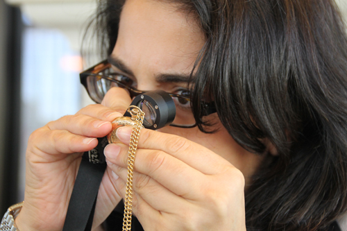 PAUL SQUIRE PHOTO | Appraiser Karen Sampieri examines a gold pocketwatch during Saturday's appraisal event in Riverhead. The watch was valued at between $400 and $1,000.