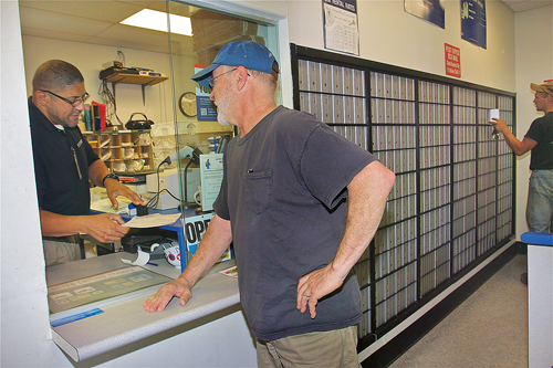 Postmaster Kevin Ford helps South Jamesport resident Dan Faraone Tuesday morning. (Credit: Barbaraellen Koch)